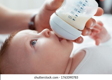 cropped view of man feeding adorable infant from baby bottle with milk