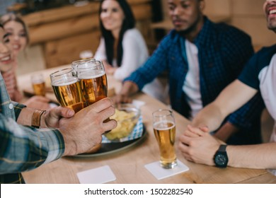 cropped view of man holding glasses of light beer near multicultural friends in pub