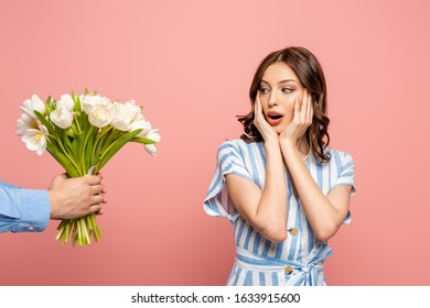 cropped view of man presenting bouquet of white tulips to surprised young woman isolated on pink