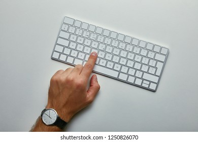 Cropped view of man pushing button on computer keyboard on grey background