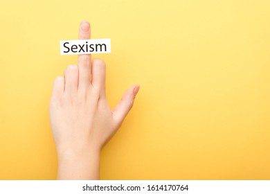 cropped view of man showing middle finger with card sexism isolated on yellow