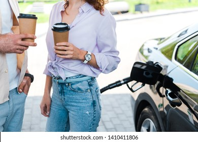 cropped view of man standing with hand in pocket near woman holding paper cup at gas station
