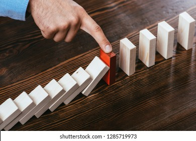 cropped view of man touching red brick and preventing wooden blocks from falling