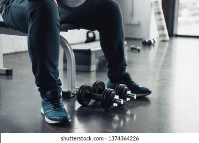 cropped view of man in trainers sitting with dumbbells at sports center