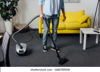 Cropped view of man using vacuum cleaner while cleaning carpet in living room