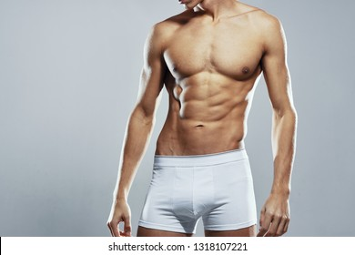 cropped view of a man in white shorts on a gray background port fitness figure diet nutrition pumped body exercise strong torso underwear and waist