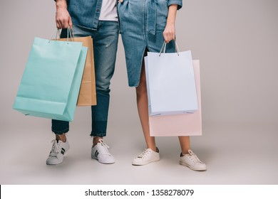 cropped view of man and woman holding shopping bags on grey background