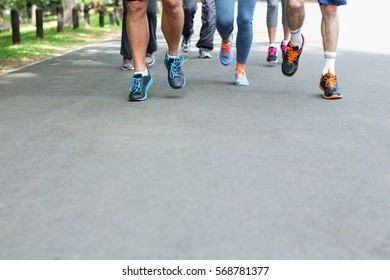 Cropped view of marathon athletes feet running on the street