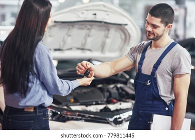 cropped view of mechanic giving car keys to female client.