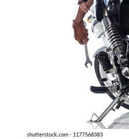 Cropped view of Mechanic using a wrench on a motorcycle on white background