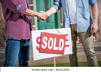 cropped view of men shaking hands with saleman and buying new house