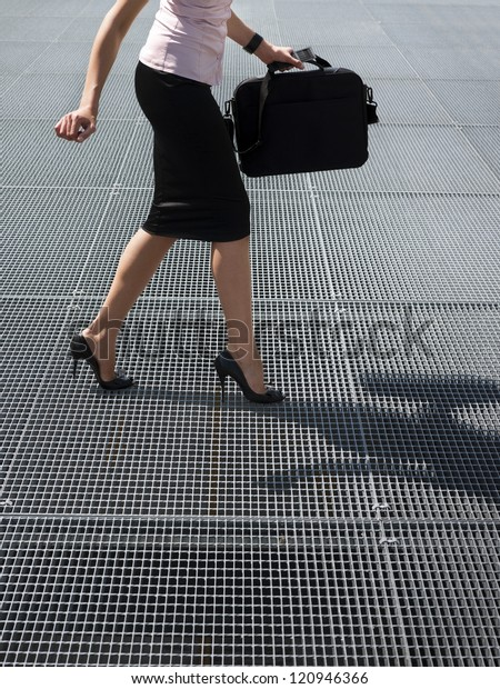 cropped view of mid adult business woman walking on high heels, trying to balance on grating