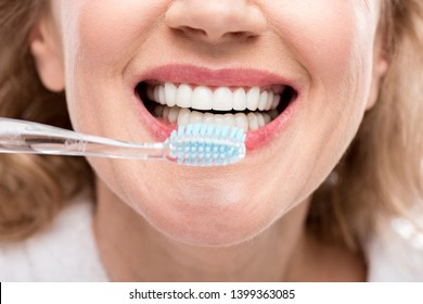 Cropped view of middle aged woman brushing Teeth Isolated On White