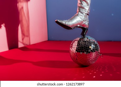 cropped view of model in metallic footwear posing with disco ball on pink and blue background