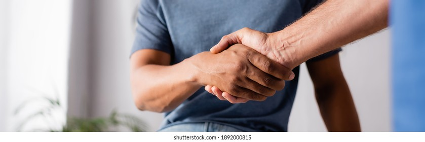 cropped view of multicultural men shaking hands in clinic, banner