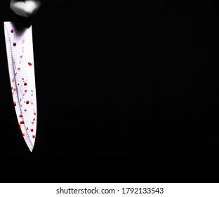 cropped view of murderer holding knife in blood. Dark background. Blood. Knife.
