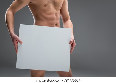 cropped view of naked man holding blank placard, isolated on grey