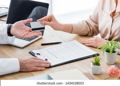 cropped view of patient at table with insurance claim form giving credit card to doctor