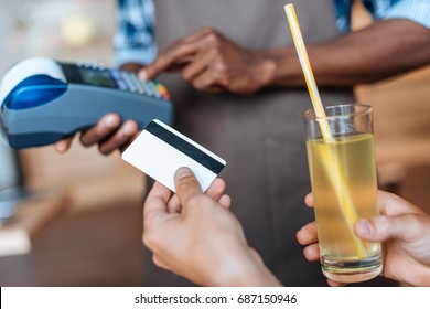 cropped view of person paying with credit card, waiter with terminal standing behind in cafe