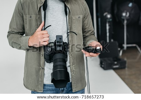cropped view of professional male photographer with digital photo camera and light meter in photo studio