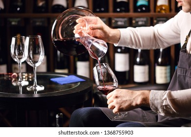 Cropped view of professional sommelier pouring red wine from bottle into decanter at table in wine restaurant.