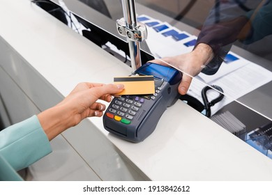 Cropped view of receptionist holding payment terminal near woman with credit card in hotel