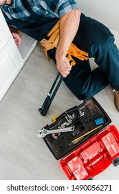 cropped view of repairman working near kitchen cabinet and toolbox with instruments