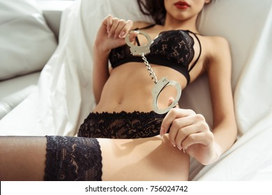 cropped view of seductive woman posing in black sexy lingerie with handcuffs on sofa