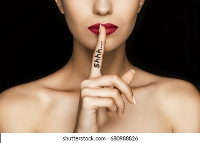 cropped view of seductive woman with red lips showing shh symbol, isolated on black
