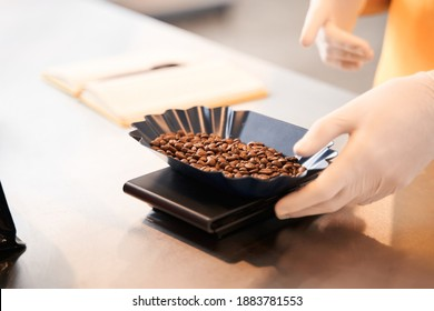 Cropped view of the seller in uniform weighing coffee beans before the filling bags with coffee beans working in the coffee store. Stock photo