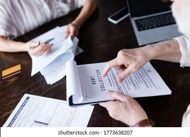 Cropped view of senior man pointing at paper with debt collection lettering near gadgets and wife at home