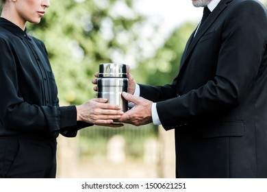 cropped view of senior man and woman holding mortuary urn