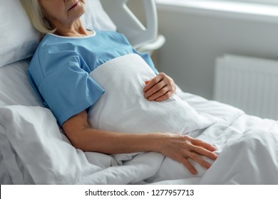 cropped view of senior woman lying in hospital bed