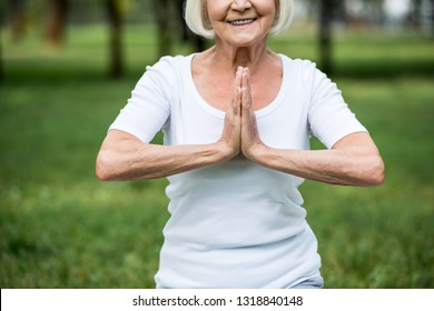 cropped view of senior woman in meditation sukhasana sitting pose with folded hands