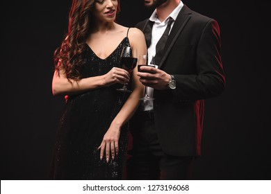 cropped view of sexy couple clinking glasses with red wine isolated on black