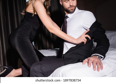 Cropped view of sexy woman in dress taking off jacket from boyfriend on bed in hotel