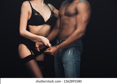 cropped view of shirtless african american man in handcuffs and sexy woman in lingerie isolated on black