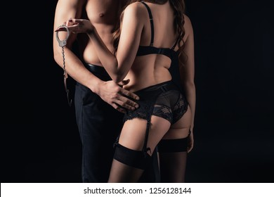 cropped view of shirtless man embracing woman in lingerie holding handcuffs isolated on black