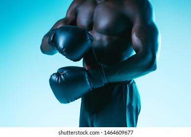 cropped view of shirtless, muscular african american sportsman in boxing gloves on blue background