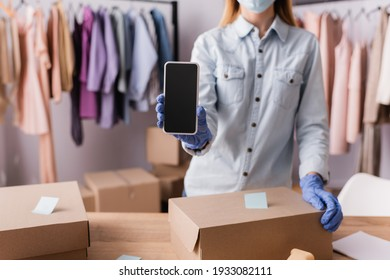 cropped view of showroom proprietor in latex gloves holding smartphone near boxes on blurred foreground