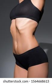 cropped view of slim woman in black underwear on dark background