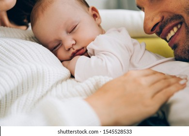 cropped view of smiling father leaning on adorable baby lying on mothers hands