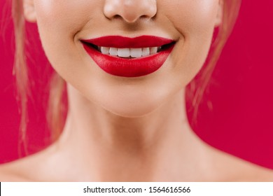 cropped view of smiling naked beautiful woman with red lips isolated on red