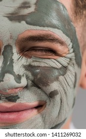 cropped view of smiling young man with clay mask with closed eye