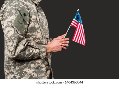 cropped view of soldier holding american flag isolated on grey