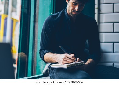 Cropped view of stylish casual dressed young man author writing down text blog article in notepad sitting in coffee shop interior.Pensive student in black shirt noting checklist in notebook