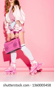 cropped view of stylish girl holding retro boombox while standing in roller-skates on pink