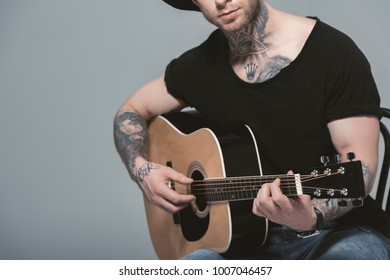 cropped view of tattooed man playing acoustic guitar, isolated on grey