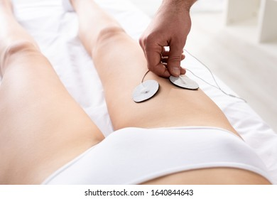 Cropped view of therapist setting electrode on leg of patient during electrode treatment