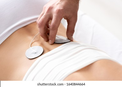 Cropped view of therapist setting electrode on patient back during electrode treatment on grey background